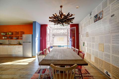 פינת האוכל משקיפה החוצה וזולגת אל המטבח. נברשת עץ: one bedroom, יפו.