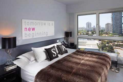 חדר שינה בעיצוב עכשווי עם כיסוי מיטה מפרווה מלאכותית ואמנות טיפוגרפית